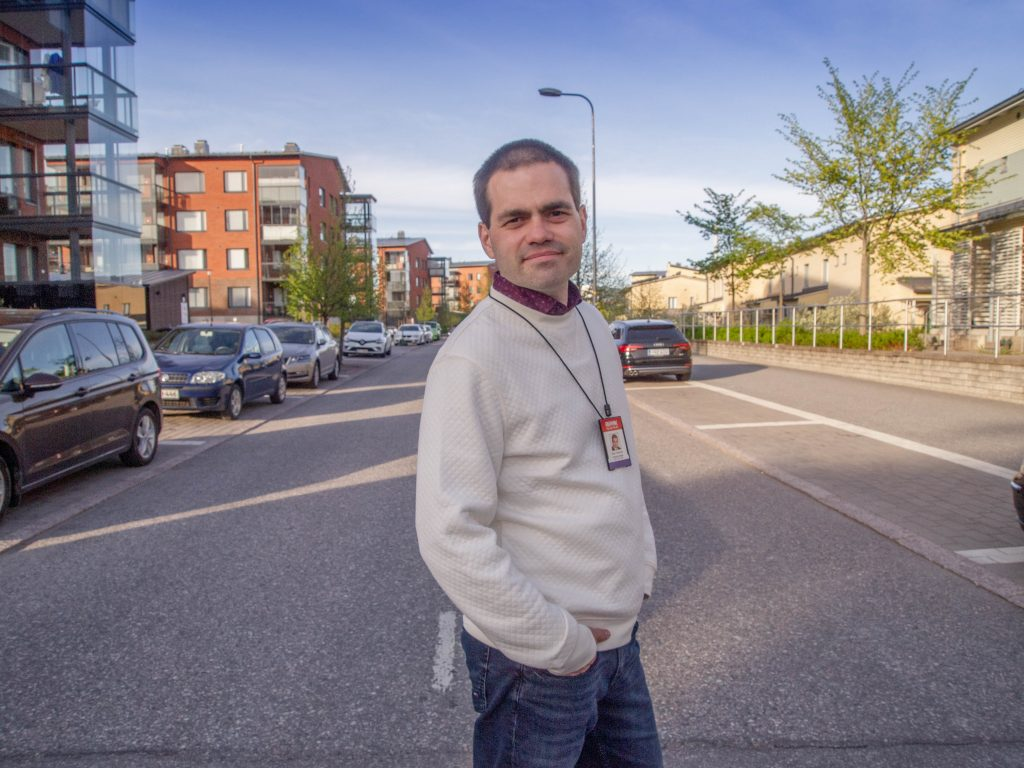Kuvassa Sam Kamras kerrostaloalueen kadulla.