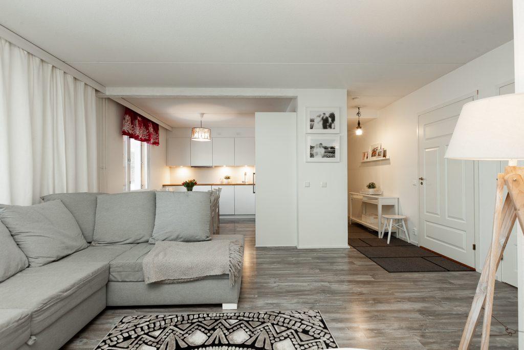 Olohuone ja avokeittiö asunnossa, jossa valkoiset seinät ja harmaa sisustus.